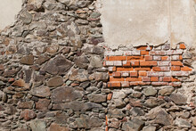 Old Brick And Stone Building Wall Along With Crumbling Plaster.