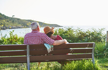 Anonymous Elderly Couple Sitting On Bench On Coast Of River