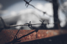 Barbed Wire Fence Against Dramatic, Dark Sky