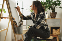 A Young Woman Artist Paints In Her Apartment With Oil Paints. Female Student Draws In Art Studio.Fine Art Study Concept.mockup Canvas