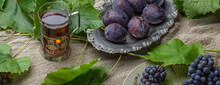 Bunches Of Blue Imperfect Garden Grapes And Plums With Leaves In Vintage Silver Dish And Black Tea In Antique Glass