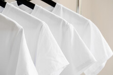 Row Of White T-shirts On Hangers On Rack