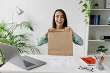 Young Fun Successful Employee Business Woman In Blue Shirt Hold Brown Clear Blank Craft Paper Takeaway Bag Mock Up Sit Work At White Desk With Laptop Computer At Office Indoors. Delivery Food Concept.