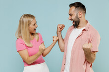 Young Fun Overjoyed Couple Two Friends Family Man Woman In Casual Clothes Do Winner Gesture Look To Each Other Scream Yes Together Isolated On Pastel Plain Light Blue Color Background Studio Portrait.
