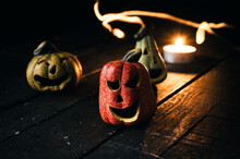 Small Ceramic Halloween Pumpkins. Decorative Jack-o'-lantern On Wooden Table. Candle And Fire Light In Background.