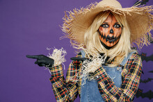 Young Woman With Halloween Makeup Mask In Straw Hat Scarecrow Costume Point Finger Aside On Area Copy Space Mock Up Isolated On Plain Dark Purple Background Studio Celebration Holiday Party Concept.
