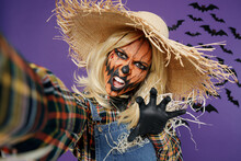 Close Up Scary Young Woman With Halloween Makeup Mask In Straw Hat Scarecrow Costume Doing Selfie Shot Pov On Mobile Phone Isolated On Plain Dark Purple Background Studio Celebration Holiday Concept.