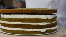 A Male Pastry Chef In White Clothes And Black Gloves Puts A Cake Made Of Green Spinach Cakes And Applies Cream And Wait. Slaps And Flattens The Sponge Cake. Dolly Shot, Close Up