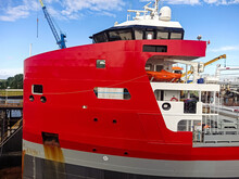 Stern Superstructure Of A Dry Cargo Ship With A Captain's Bridge And Navigation Equipment And A Lifeboat. Dry Cargo Ship In Dry Dock At A Shipyard. Red Seagoing Vessel For Commercial Cargo Delivery