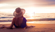 Attractive Woman On Beach. Summer Holiday Fashion Concept Woman Wearing Sun Hat At The Beach On Sand Shot From Above Happiness Sexy Girl At Sunset Time. Summrer Travel Or Vacation Concept.