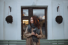 Middle-aged Brunette Woman Walking Down The Street In Autumn With A Mug Of Hot Coffee