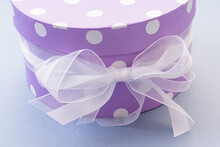 Round Purple Gift Box With A Ribbon On Blue Background. Gift Packaging. Close Up