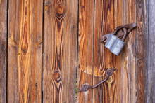 An Old Forged Zosvo With A Hinged Lock And An Old Forged Rusty Door Handle Nailed To The Door. Texture Of An Old Wooden Fence In A Village With Rusty Nails.