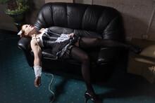 Crime Scene Imitation. Strangled Chambermaid Lying On The Couch.