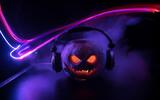 Fototapeta Kawa jest smaczna - Halloween pumpkin on a dj table with headphones on dark background with copy space. Happy Halloween festival decorations