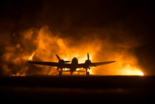 German Junker (Ju-88) Night Bomber At Night. Artwork Decoration With Scale Model Of Jet-propelled Plane In Possession. Toned Foggy Background With Light. War Scene.