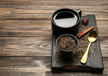 Board With Dry Hojicha Green Tea And Cup Of Hot Beverage On Wooden Background