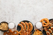 canvas print picture - Mugs of cold beer, plates with Bavarian sausages and snacks on light background. Oktoberfest celebration