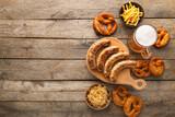 Mug of cold beer, board with Bavarian sausages and snacks on wooden background. Oktoberfest celebration
