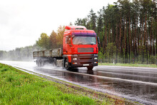 A Red Flatbed Semitrailer Tractor Driving On The Road In Rain And Poor Visibility In Summer. Poor Visibility Concept In Bad Weather