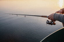 Fishing Rod With A Spinning Reel In The Hands Of A Fisherman. Fishing Background