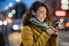 Woman On Street Using Phone At Evening