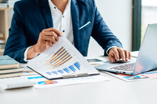Business Man Is Checking And Auditing The Business Performance With A Help From His College. Analyzing The Revenue And Auditing The Budget Concept.