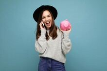 Portrait Photo Of Happy Positive Smiling Laughing Young Beautiful Brunette Woman Wearing Stylish Sweater And Black Hat Isolated Over Blue Background With Empty Space, Holds Pink Piggy Bank And Speaks