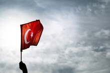 Hand Holding Turkish Flags On A Blue And Cloudy Sky And On The Day Of Liberty Izmir