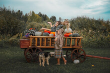 Beautiful Happy Family, Mother, Daughter And Pet Dog Together, On A Wooden Cart With Colorful Pumpkins