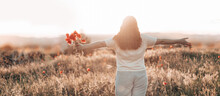 Hiking Woman Standing In Field And Watching Horizon With Beautiful Sky At Sunset. Tourism, Traveling And Healthy Lifestyle Concept.