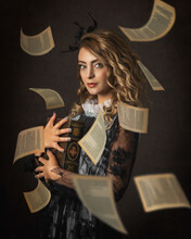 Portrait Of A Beautiful Woman Holding A Book And Flying Pages With Classic, Victorian Style Outfit And Hairstyle On Dark Background