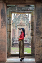 Portrait Asian Woman In Thai Tradition Clothing Posting In Front Of The Gate Of Prasat Muang Tam, Prasat Muang Tam Is A Khmer Hindu Temple In Buriram Province, Thailand