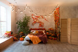 Autumn bedroom, living room interior. Red and yellow leaves and flowers in the vase and pumpkin on light background.
