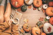 Autumn Background With Woman Sitting Between Pumpkins, Top View