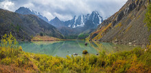 Autumn Sunny Alpine Landscape With Beautiful Shallow Mountain Lake With Streams In Highland Valley From Bigger Mountains Under Cloudy Sky. Upper Shavlin Lake In The Altai.