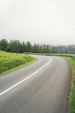 Curved Road Against Mountain In Foggy Weather
