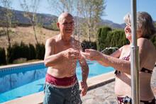 Smiling Senior Couple Having Shower On Poolside