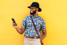 Stylish Black Man With Tattoos Chatting On Smartphone