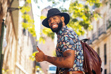 Cheerful Black Traveler With Tattoos Showing Like Gesture In Town