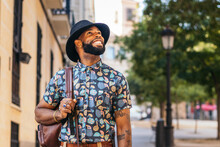 Stylish Black Hipster Man In Hat Between Urban Buildings