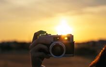 Faceless Photographer Taking Photo Of Sunset On Old Camera
