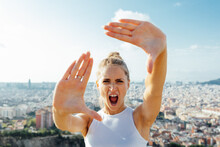 Sportswoman Screaming While Showing Frame Gesture During Workout In City