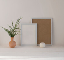 A Mock-up Of Two Empty White Frames For Paintings Or Photos, A Ceramic Vase With Green Thuja Branches, A Candlestick On A Wooden Table Against A Light Wall Background.