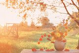 bouquet autumn flowers in rustic jug on wooden table outdoor at sunset