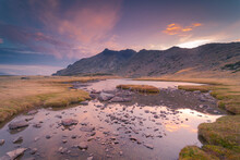 Picturesque Landscape Of River Against Mountains Under Colorful Sky At Sunset
