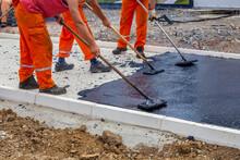 Workers Leveling Hot Asphalt