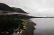 Aerial shot of a foggy morning over the rural town surrounded by lake and mountains in Alaska