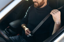 Close Up View Of The Caucasian Young Bearded Man In A Car Fastening His Seat Belts Before The Driving. Confident Guy Riding At The Work. Stock Photo