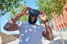 A Dark-skinned Man In A White Tshirt In Vr Glasses Looking Excited
